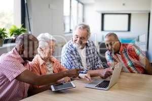Happy senior men and woman using laptop