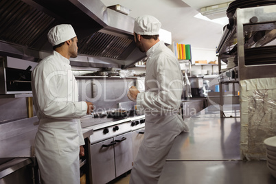 Chefs interacting with each other in kitchen
