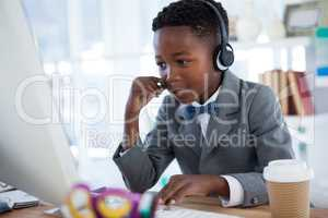 Businessman wearing headphone while using computer