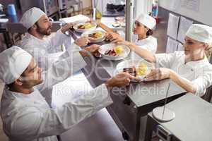 Chefs passing ready food to waiter at order station