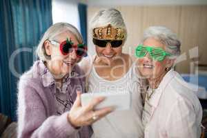 Senior women wearing novelty glasses taking selfie through smart phone