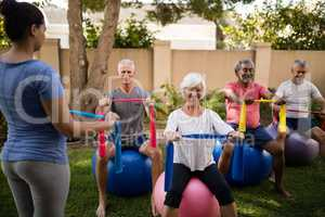 Trainer guiding senior people while exercising with ribbons and balls
