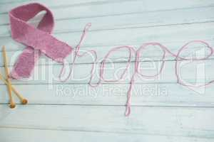 High angle view of pink Breast Cancer Awareness ribbon by hope text and crochet needles