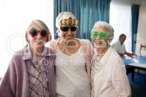 Smiling senior women wearing novelty glasses