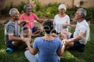 Trainer holding hands and meditating with senior men and women