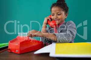 Smiling businesswoman dialing numbers on land line phone