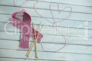 High angle view of pink woolen Breast Cancer Awareness ribbon by crochet needles with heart shape
