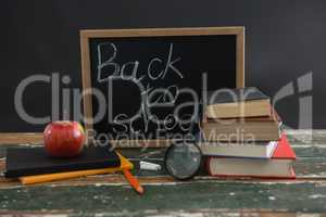 Back to school text written on chalkboard with various stationery and apple