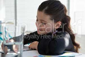 Close up of smiling businesswoman reading document at desk