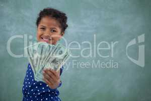 Portrait of happy girl showing paper currency