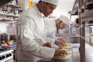 Two chefs garnishing food in commercial kitchen