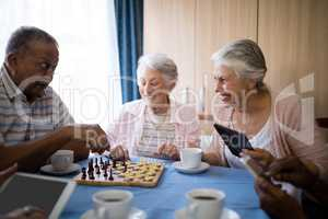 Happy senior friends playing chess while having coffee