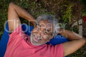 Portrait of smiling senior male resting while lying on exercise mat