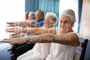 Portrait of smiling senior woman exercising with friends