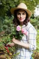 Woman trimming flowers with pruning shears in garden on a sunny day