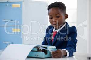 Boy imitating as businessman working on typewriter