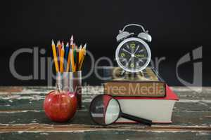 Alarm clock on stack of books with pen holder, apple, and magnifying glass
