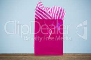 Close-up of vibrant pink Breast Cancer Awareness ribbon on shopping bag over wooden table