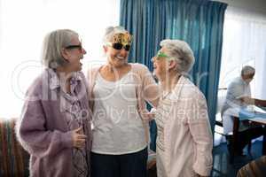 Senior female friends wearing novelty glasses talking at nursing home