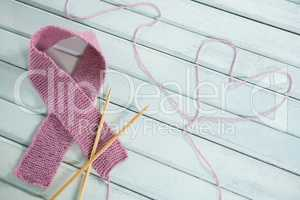Close-up of pink Breast Cancer Awareness ribbon by crochet needles with heart shape