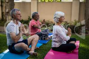 Senior people meditating in prayer position