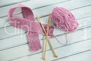 High angle view of pink woolen Breast Cancer Awareness ribbon with crochet needles