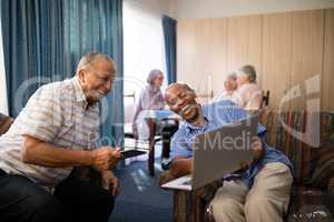 Happy senior friends looking at laptop