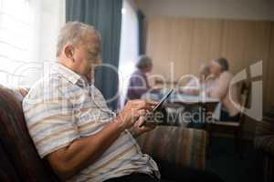 Senior man using mobile phone on sofa