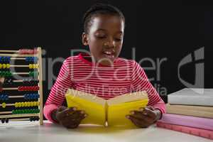 Schoolgirl reading a book against black background