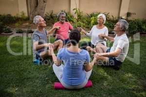 Trainer and senior people meditating while holding hands