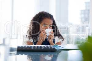 Businesswoman with curly hair looking away while drinking coffee