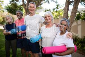 Portrait of happy multi-ethnic friends carrying exercise mats