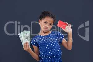 Portrait of girl showing currency and credit card