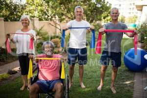 Portrait of senior couple holding multi colored ribbons