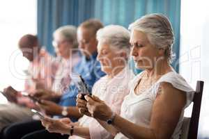 Row of senior people sitting on chairs using digital tablets