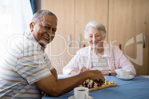 Smiling senior man playing chess with friend