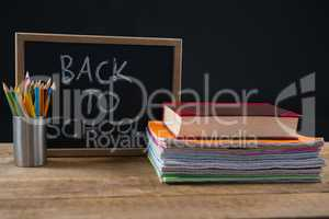 Back to school text written on chalkboard with book stack and pen holder
