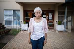 Portrait of serious senior woman standing on entrance