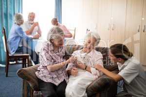 Senior friends and female doctor stroking kitten