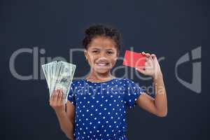 Portrait of girl showing credit card and currency