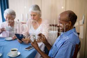 Senior man playing cards with friends while having coffee