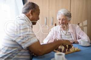 Smiling male and female seniors playing chess at table