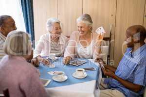 Happy senior people enjoying tea while playing cards