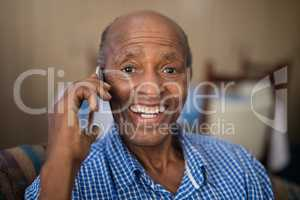Portrait of cheerful senior man talking on mobile phone