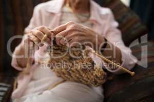 Midsection of senior woman knitting wool while sitting on sofa