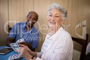 Portrait of senior woman playing cards with friend