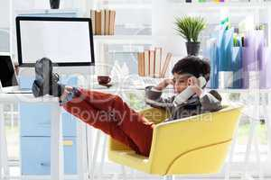 Full length of business talking on smart phone while sitting on armchair