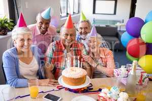Portrait of cheerful senior friends celebrating birthday