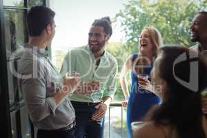Group of friends interacting with each other while having cocktail drink