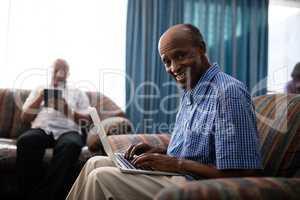 Portrait of senior man using laptop